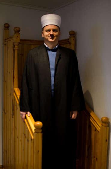 Dervis Vareslija står i «prekestolen» i moskeens bønnerom. Han bruker hatten og kåpen når han leder bønnen.